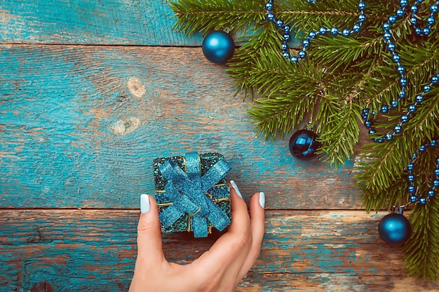 Womans hands holding noël ou nouvel an boîte-cadeau décorée sur fond de noël décoré vue de dessus