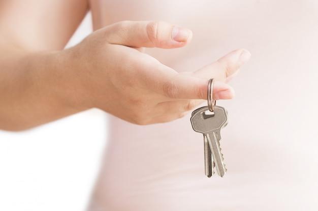 Womans main avec clé en métal. touches à la main sur fond blanc. isolé sur blanc