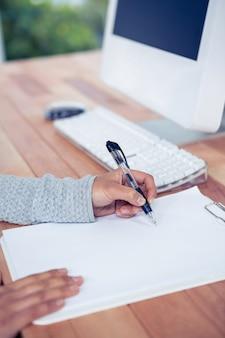 Womans main écrivant avec un stylo sur une feuille blanche au bureau