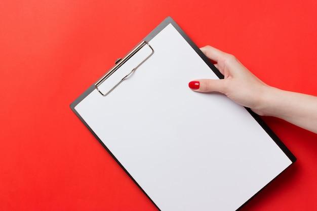 Womans mains avec des clous rouges, tenant un presse-papiers noir sur fond rouge