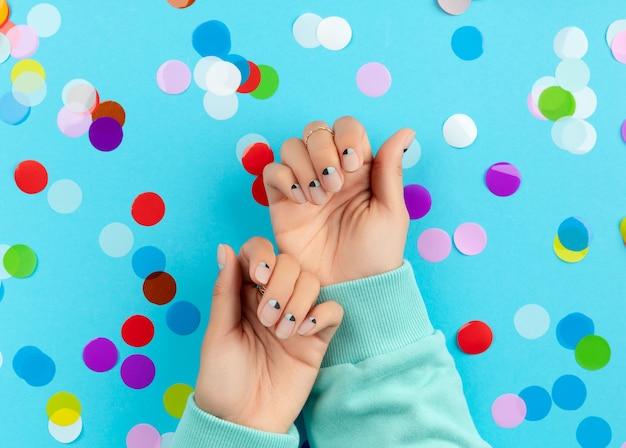 Womans mains avec des confettis colorés sur fond bleu. concept de salon de beauté mode spa