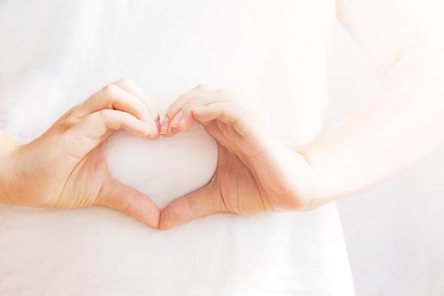 Womans les mains en forme de coeur. mains sur fond blanc