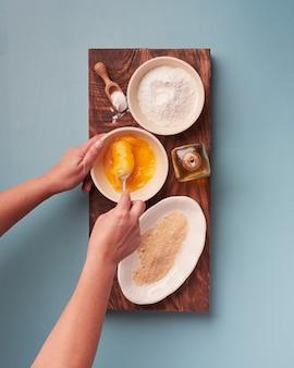 Womans mains tenant une fourchette pour battre les œufs avec divers ingrédients de cuisine sur une planche de bois placée sur une planche de bois rectangle foncé
