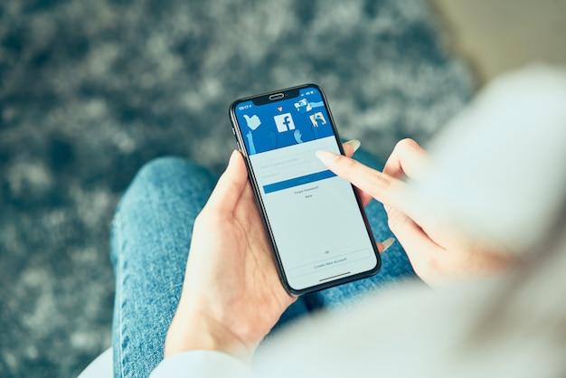 Womans tenant à la main et appuyant sur l'écran facebook du téléphone intelligent apple.