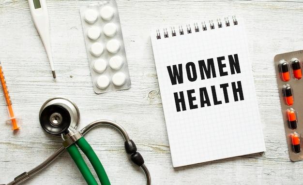 Women health est écrit dans un cahier sur un tableau blanc à côté de pilules et d'un stéthoscope.