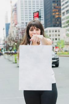 Wonan tenant un sac à provisions blanc à la main
