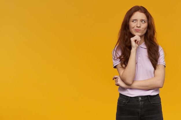 Wonder fille à la recherche, jolie femme rousse aux cheveux longs. porter un t-shirt rose. concept d'émotion. toucher son menton et rêver. regarder vers la gauche à l'espace de copie, isolé sur un mur orange