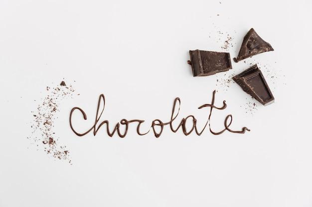 Word chocolat près de morceaux de chocolat et de miettes
