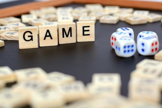 Word game avec des lettres en bois sur un tableau noir avec des dés et une lettre dans le cercle