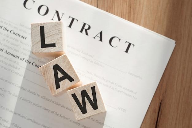 Word loi sur des cubes en bois sur fond de documents contractuels