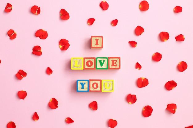 Word love avec des pétales de rose sur fond rose
