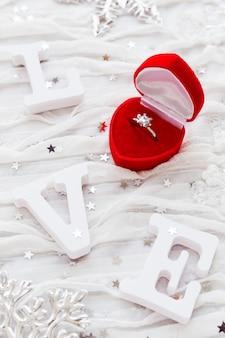 Word love sur un tissu blanc avec une bague de fiançailles en diamant dans une boîte cadeau rouge. bon pour les cartes de saint valentin.