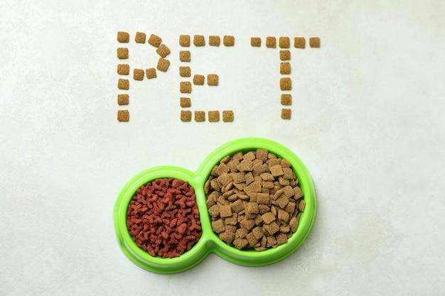 Word pet fait de nourriture et bols de nourriture sur blanc texturé