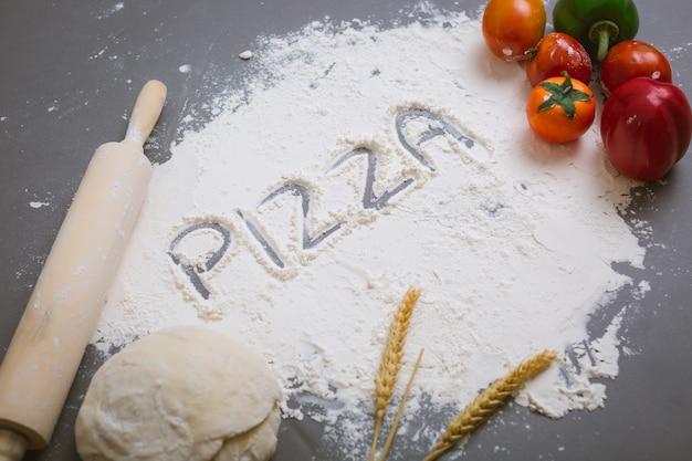 Word pizza écrit sur de la farine avec des ingrédients