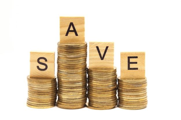 Word save concept sur bloc de bois sur les pièces de monnaie empilées.