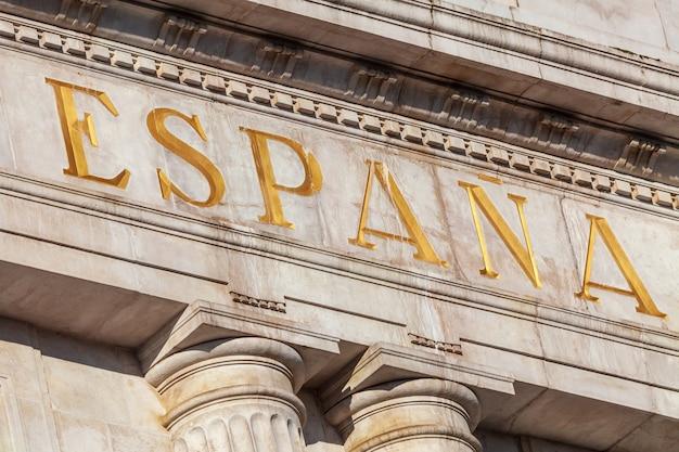 Word spain en espagnol sculpté dans la pierre et la couleur dorée