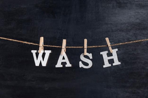 Word wash avec des pinces à linge sur fond noir. concept de service de blanchisserie.