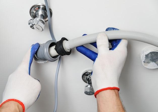 Workman attache un tuyau de vidange à un tuyau d'égout.
