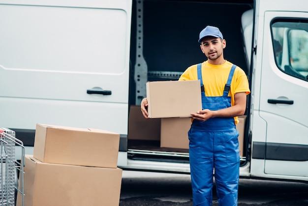 Workman ou courrier détient une boîte en carton dans les mains