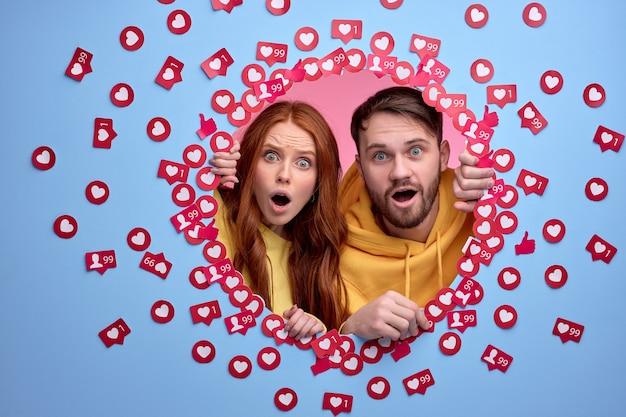 Wow. couple caucasien sous le choc par les nouvelles et aime sur le poste, se tenir debout avec la bouche et les yeux ouverts