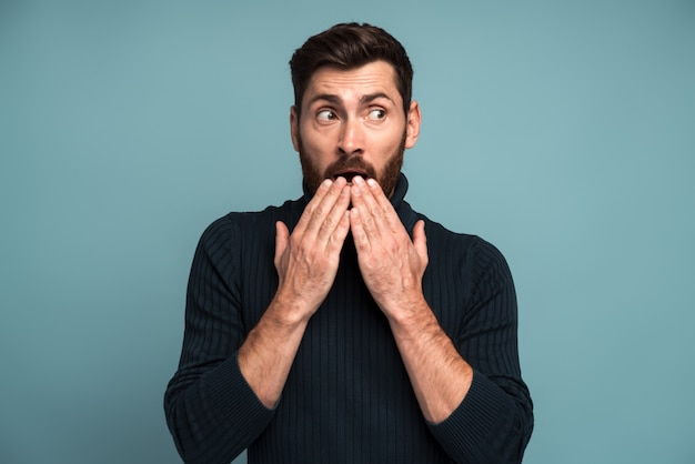 Wow. homme couvrant la bouche avec la main et détournant les yeux avec de grands yeux, expression surprise effrayée, choqué par une nouvelle soudaine. studio intérieur tourné isolé sur fond bleu