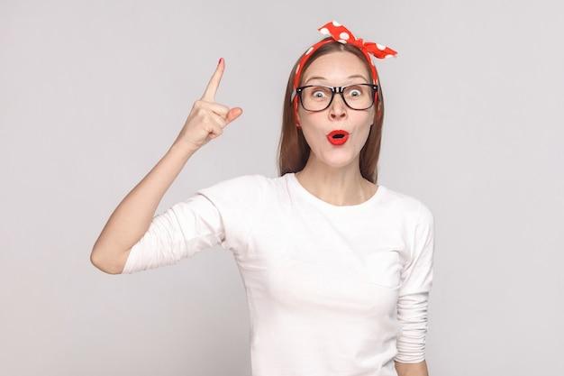 Wow. j'ai une idée. portrait d'une belle jeune femme émotive en t-shirt blanc avec taches de rousseur, lunettes noires, lèvres rouges et bandeau. tourné en studio intérieur, isolé sur fond gris clair.