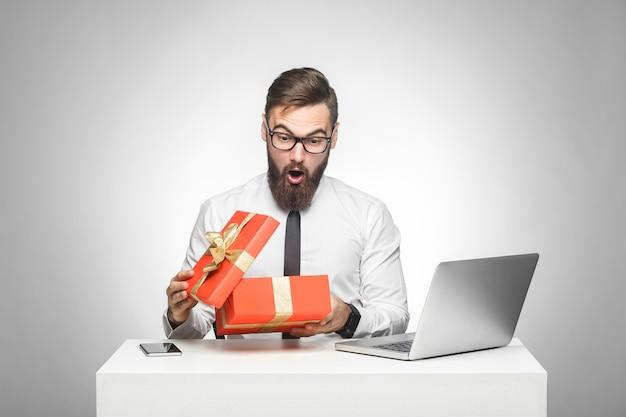 Wow! un jeune manager surpris en chemise blanche et cravate noire est assis dans son bureau et déballe un présent avec un visage choqué, de grands yeux et une bouche ouverte. intérieur, isolé, tourné en studio, fond gris