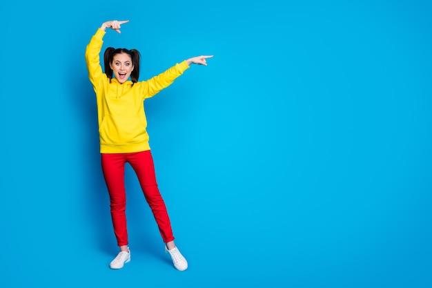 Wow. photo complète du corps d'une dame assez drôle deux queues côté doigts directs espace vide vente bannière commerciale porter un pull à capuche jaune décontracté pantalon rouge isolé fond de couleur bleu vif