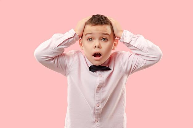 Wow. portrait de face mâle attrayant demi-longueur sur fond rose. jeune garçon adolescent surpris émotionnel debout avec la bouche ouverte
