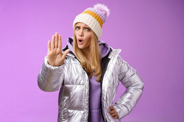 Wow, ralentissez, attendez sec. une fille blonde dérangée, mécontente, lève la main, arrête un geste d'interdiction suffisant en secouant la tête négativement, décline une idée terrible de ne pas donner la permission, fond violet.