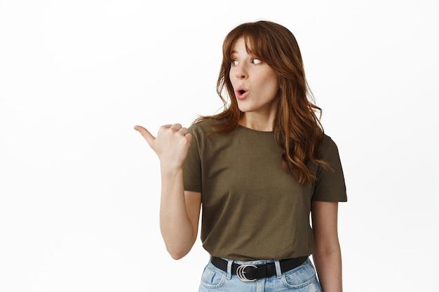 Wow, regarde ça. jeune femme impressionnée pointant vers la gauche et regardant la publicité debout sur blanc