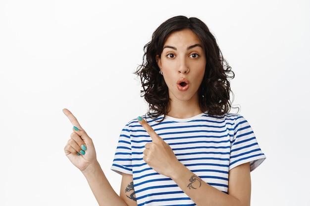 Wow regarde par ici. une femme brune étonnée a l'air impressionnée, pointant vers la gauche la bannière du logo, montrant une publicité sur un espace vide, debout en blanc