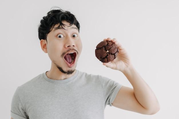 Wow et le visage choqué de l'homme se sent excité avec l'énorme biscuit au chocolat