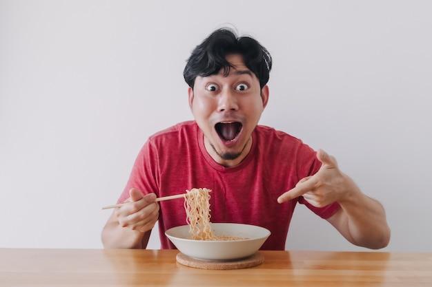 Wow et visage drôle surpris de l'homme mangeant des nouilles instantanées