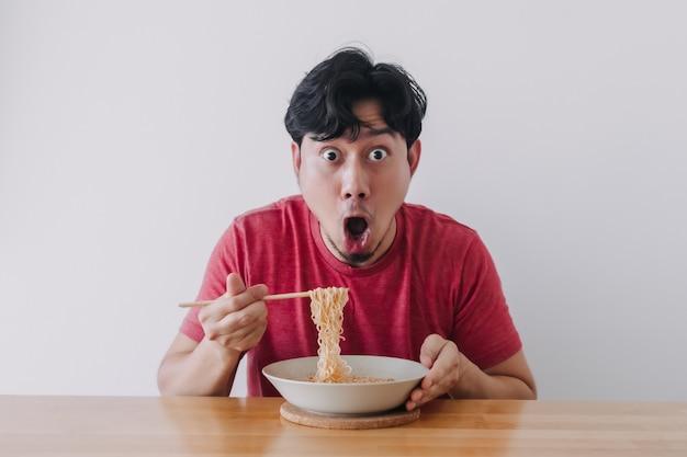 Wow et visage drôle surpris de l'homme mangent des nouilles instantanées