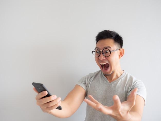 Wow visage de l'homme a choqué ce qu'il voit dans le smartphone.