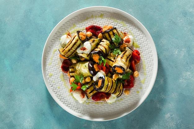 Wrap d'aubergines grillées avec houmous aux poivrons rouges et yogourt épicé sur la table. délicieuse recette végétalienne