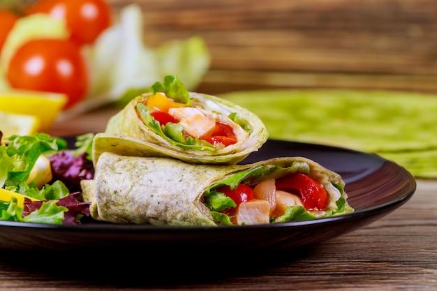 Wrap d'épinards avec de la viande et des légumes sur une plaque noire avec une salade verte.