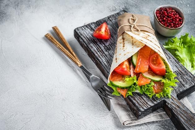 Wrap sandwich, roulé avec poisson saumon et légumes. fond blanc. vue de dessus. espace de copie.