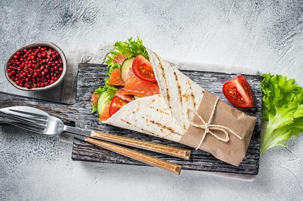 Wrap sandwich, roulé avec poisson saumon et légumes. fond blanc. vue de dessus.