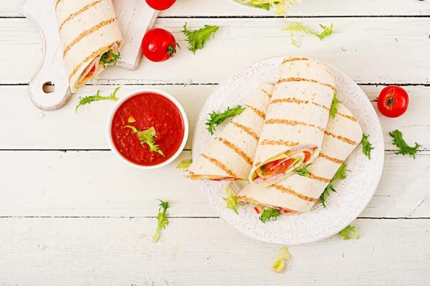 Wrap de tortilla au jambon, fromage et tomates sur une table en bois blanc. vue de dessus
