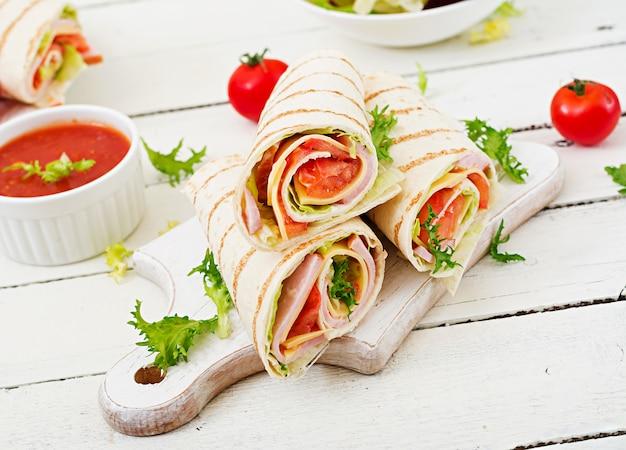 Wrap de tortilla au jambon, fromage et tomates sur une table en bois blanc