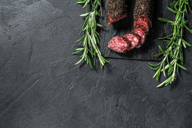 Wurst, fuet, tranches de saucisse. saucisse de porc. mur noir. vue de dessus