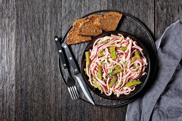 Wurstsalat allemand de saucisse de lyoner allemande cuite avec concombres marinés, tranches d'oignon rouge, vinaigrette servie sur un bol noir sur un fond en bois foncé avec de la moutarde, vue de dessus, gros plan
