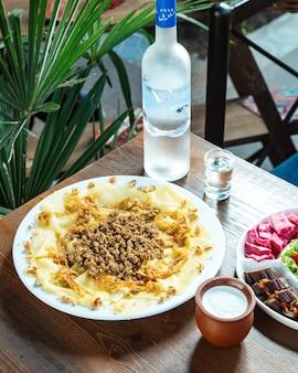 Xhinkali avec vue de côté de la vodka à la viande de yogourt nature