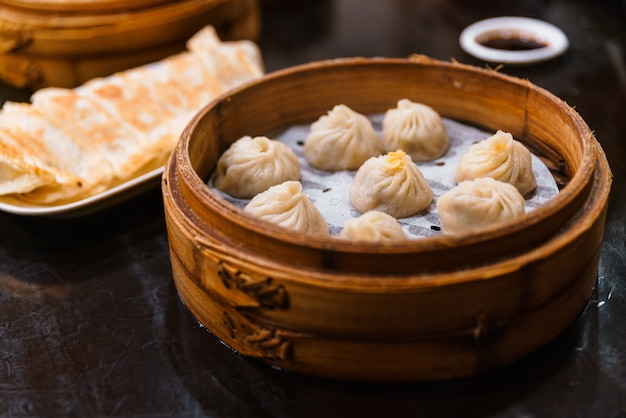 Xiao long bao cuit à la vapeur (quenelles de soupe) dans the bamboo basket. servi au restaurant à taipei, taiwan.