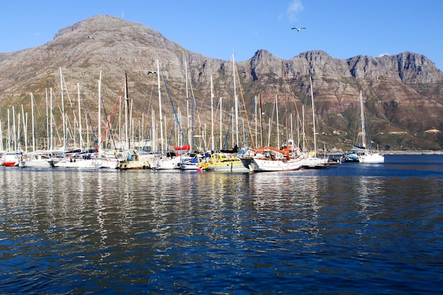Yacht amarré dans la mer bleu foncé près de la montagne