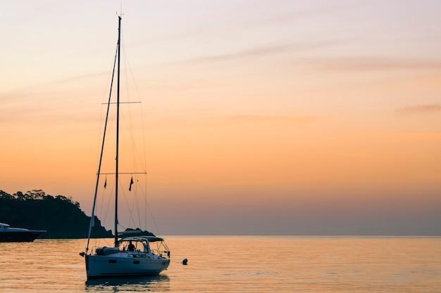 Yacht au coucher du soleil un yacht dans la baie de la mer dans le contexte d'un beau coucher de soleil