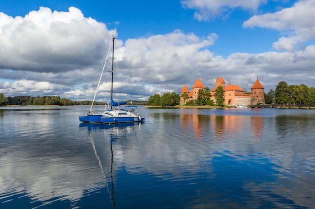 Yacht bleu sur le lac galve, lituanie avec le château de trakai sur fond