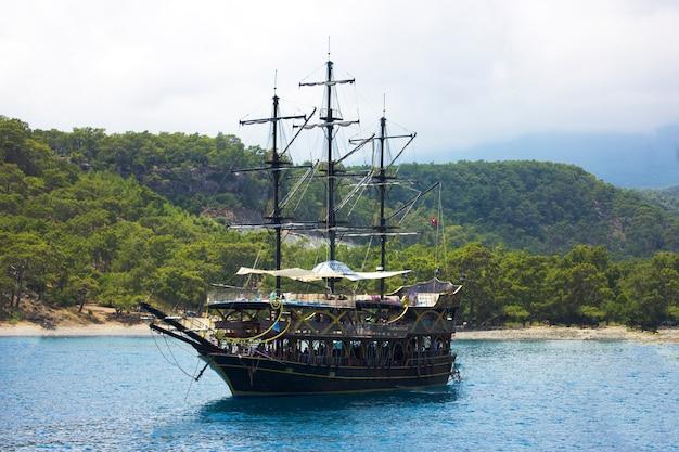 Yacht en bois dans la mer méditerranée bleue calme dans un lagon vert avec des montagnes